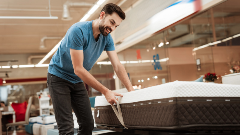 A Man Trying How Effective an Ottoman Bed Is During a Product Presentation